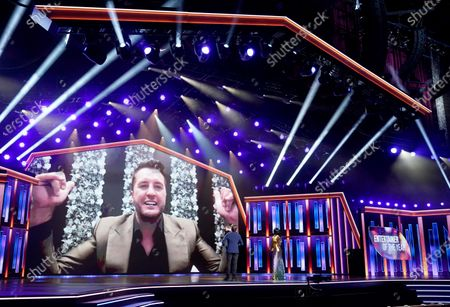 Luke Bryan appears on screen accepting the award for entertainer of the year at the 56th annual Academy of Country Music Awards, at the Grand Ole Opry in Nashville, Tenn. Looking on from left are hosts Mickey Guyton and Keith Urban