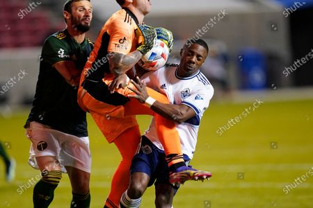 Portland Timbers goalkeeper Steve Clark, center, collides with Vancouver Whitecaps FC forward Cristian Dajome, right, after making a save in the second half of an MLS soccer game, in Sandy, Utah