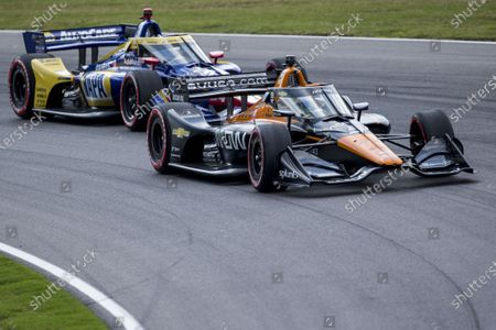Schmidt Peterson Motorsports driver Pato O'ward (5) takes the second turn ahead of Andretti Autosport driver Alexander Rossi (27) during the Honda Indy Grand Prix of Alabama auto race at Barber Motorsports Parkway, in Birmingham, Ala