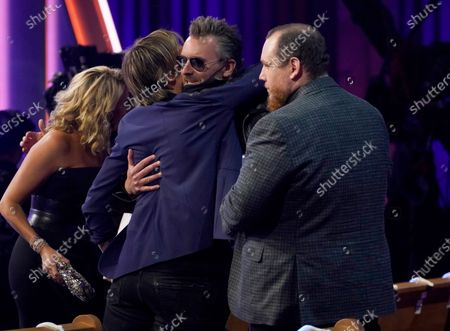 Keith Urban, from left, Eric Church and Luke Combs speak in the audience at the 56th annual Academy of Country Music Awards, at the Grand Ole Opry in Nashville, Tenn