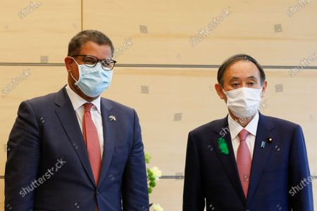 President Alok Sharma, left, and Japan's Prime Minister Yoshihide Suga pose for the cameras at the prime minister's official residence in Tokyo