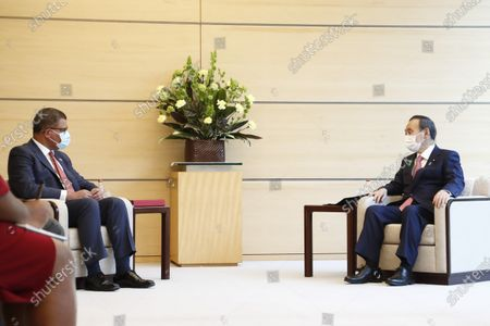 Japan's Prime Minister Yoshihide Suga, right, meets COP26 President Alok Sharma at the prime minister's official residence, in Tokyo, Japan
