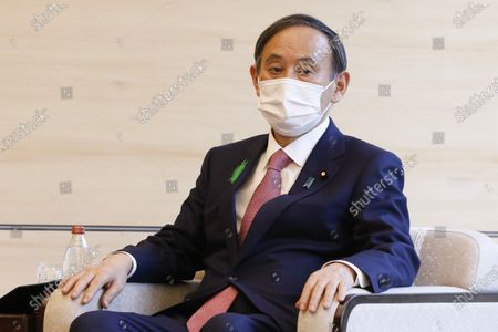 Japan's Prime Minister Yoshihide Suga wearing a face mask meets COP26 President Alok Sharma at the prime minister's official residence, in Tokyo, Japan
