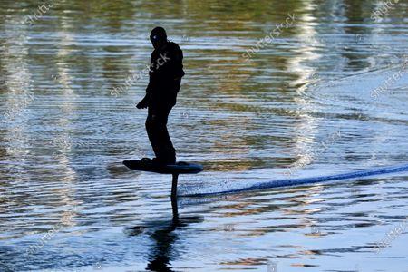 Man on a water hoverboard, River Thames, Hampton Court Bridge, London