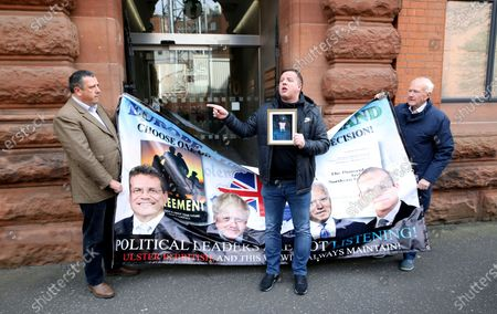 David Campbell, left, and David McNarry, right, of the Loyalist Communities Council have their protest interrupted by Gareth McCord outside the offices of the Irish government secretariat in Belfast, Northern Ireland, . Gareth McCord's brother Raymond was murdered by Loyalist paramilitaries in 1997. The LCC represents the paramilitary groups the Ulster Volunteer Force, Ulster Defence Association and Red Hand Commando, the peaceful protest was against the NI Protocol