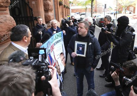 Stock Picture of David Campbell, left, and David McNarry, centre left, of the Loyalist Communities Council have their protest interrupted by Gareth McCord, centre, outside the offices of the Irish government secretariat in Belfast, Northern Ireland, . Gareth McCord's brother Raymond was murdered by Loyalist paramilitaries in 1997. The LCC represents the paramilitary groups the Ulster Volunteer Force, Ulster Defence Association and Red Hand Commando, the peaceful protest was against the NI Protocol