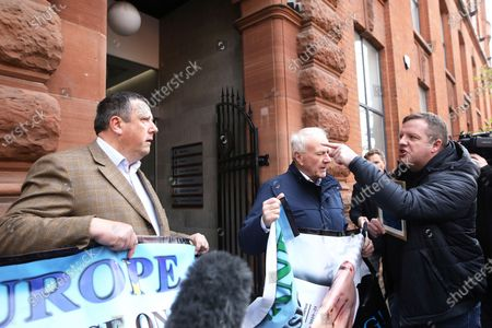 David Campbell, left, and David McNarry, second right, of the Loyalist Communities Council have their protest interrupted by Gareth McCord, right, outside the offices of the Irish government secretariat in Belfast, Northern Ireland, . Gareth McCord's brother Raymond was murdered by Loyalist paramilitaries in 1997. The LCC represents the paramilitary groups the Ulster Volunteer Force, Ulster Defence Association and Red Hand Commando, the peaceful protest was against the NI Protocol