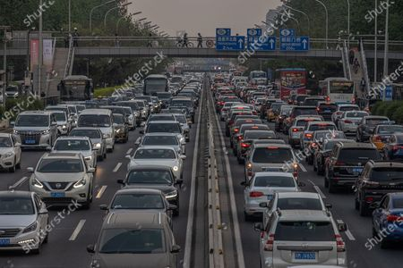 Cars drive during an evening rush hour, in Beijing, China, 19 April 2021. China and the US, the world's two biggest carbon polluters, have agreed on co-operating together to tackle climate change ahead of the Climate Summit on 22 April 2021. The countries have issued a joint statement after several meetings in Shanghai between Chinese climate envoy Xie Zhenhua and US Special Presidential Envoy for Climate John Kerry.