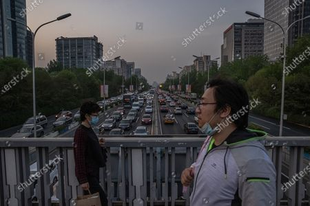 People walk on a bridge over a road with cars driving during an evening rush hour, in Beijing, China, 19 April 2021. China and the US, the world's two biggest carbon polluters, have agreed on co-operating together to tackle climate change ahead of the Climate Summit on 22 April 2021. The countries have issued a joint statement after several meetings in Shanghai between Chinese climate envoy Xie Zhenhua and US Special Presidential Envoy for Climate John Kerry.