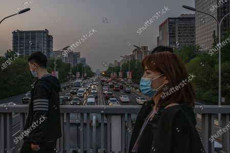 Stock Picture of People walk on a bridge over a road with cars driving during an evening rush hour, in Beijing, China, 19 April 2021. China and the US, the world's two biggest carbon polluters, have agreed on co-operating together to tackle climate change ahead of the Climate Summit on 22 April 2021. The countries have issued a joint statement after several meetings in Shanghai between Chinese climate envoy Xie Zhenhua and US Special Presidential Envoy for Climate John Kerry.
