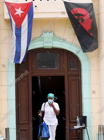 A nurse leaves a hospital adorned with Cuban and Che Guevara's flags in Havana, Cuba, 19 April 2021. Cuban President Miguel Diaz-Canel Bermudez was elected First Secretary at Cuba's communist party congress on 19 April 2021, succeeding Raul Castro who was stepping down as the leader of the party.