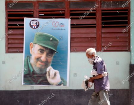 A man with a face mask walks in front a Fidel Castro poster in Havana, Cuba, 19 April 2021. Cuban President Miguel Diaz-Canel Bermudez was elected First Secretary at Cuba's communist party congress on 19 April 2021, succeeding Raul Castro who was stepping down as the leader of the party.