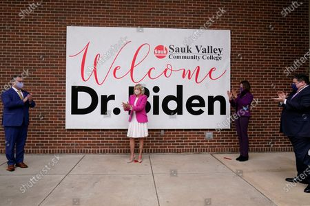 First lady Jill Biden, center, and Education Secretary Miguel Cardona, left, are welcomed by Illinois Gov. J.B. Pritzker, right, and Rep. Cheri Bustos, D-Ill., second from right, as they arrived for a visit to the Sauk Valley Community College, in Dixon, Ill