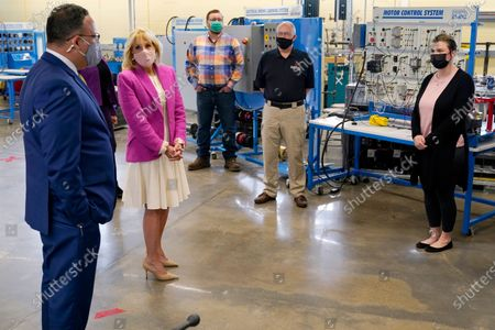 Stock Picture of First lady Jill Biden, second from left, listens as Education Secretary Miguel Cardona, left, speaks during a tour of Sauk Valley Community College, in Dixon, Ill., . SVCC student Eric Rosenow, center, SVCC Associate Professor of Electronics/Technology Steven McPherson, second from right, and SVCC graduate Crystal Collinson, right, listen