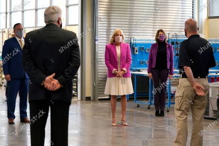 First lady Jill Biden, center, Education Secretary Miguel Cardona, left and Rep. Cheri Bustos, D-Ill., second from right, tour the Sauk Valley Community College, in Dixon, Ill