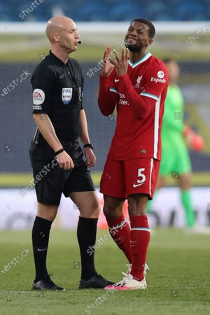 Liverpool's Georginio Wijnaldum, right, reacts in front of the referee during the English Premier League soccer match between Leeds United and Liverpool at the Elland Road stadium in Leeds, England
