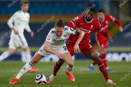 Leeds United's Luke Ayling, left, fights for the ball with Liverpool's Georginio Wijnaldum during the English Premier League soccer match between Leeds United and Liverpool at the Elland Road stadium in Leeds, England
