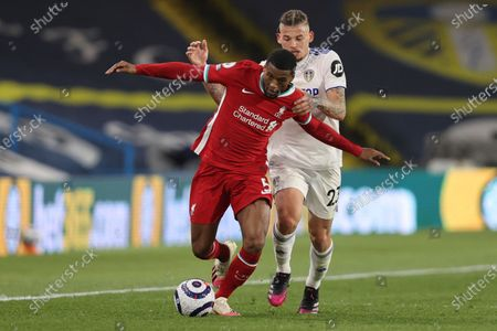 Liverpool's Georginio Wijnaldum, left, is challenged by Leeds United's Kalvin Phillips during the English Premier League soccer match between Leeds United and Liverpool at the Elland Road stadium in Leeds, England