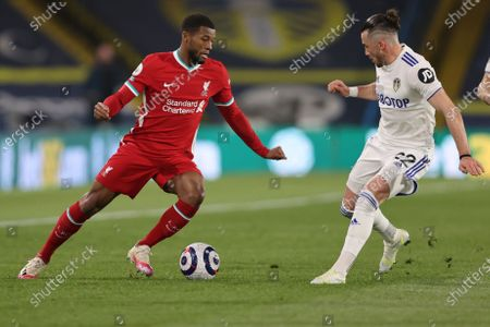 Liverpool's Georginio Wijnaldum, left, is challenged by Leeds United's Jack Harrison during the English Premier League soccer match between Leeds United and Liverpool at the Elland Road stadium in Leeds, England