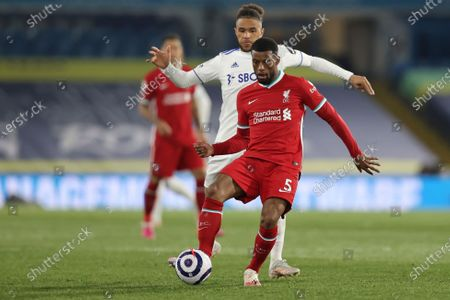 Liverpool's Georginio Wijnaldum is challenged by Leeds United's Tyler Roberts, rear, during the English Premier League soccer match between Leeds United and Liverpool at the Elland Road stadium in Leeds, England