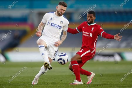 Leeds United's Stuart Dallas, left, is challenged by Liverpool's Georginio Wijnaldum during the English Premier League soccer match between Leeds United and Liverpool at the Elland Road stadium in Leeds, England