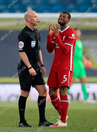 Liverpool's Georginio Wijnaldum (R) reacts while gesturing to main referee Anthony Taylor (L) during the English Premier League soccer match between Leeds United and Liverpool FC in Leeds, Britain, 19 April 2021.