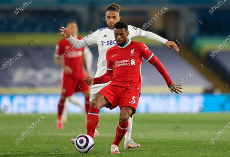 Leeds United's Tyler Roberts (L) tackles Liverpool's Georginio Wijnaldum (R) during the English Premier League soccer match between Leeds United and Liverpool FC in Leeds, Britain, 19 April 2021.