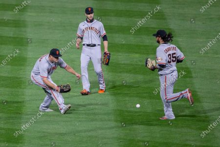 San Francisco Giants left fielder Alex Dickerson, left, center fielder Austin Slater, center, and shortstop Brandon Crawford, right, chase a ball hit for a single during the sixth inning of a baseball game, in Philadelphia