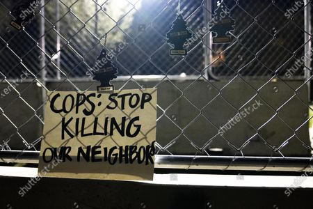 "Stock Image of A sign that reads ""COPS: STOP KILLING OUR NEIGHBORS"" hangs on fencing outside of the Brooklyn Center Police Department on April 17, 2020. Protests continued for the seventh consectutive night outside the Brooklyn Center Police Department after former officer Kim Porter killed 20-year-old Daunte Wright in a traffic stop."