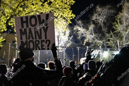 "A protester holds a sign that says ""HOW MANY MORE?"" outside the Brooklyn Center Police Department on April 17, 2020. Protests continued for the seventh consectutive night after former officer Kim Porter killed 20-year-old Daunte Wright in a traffic stop."