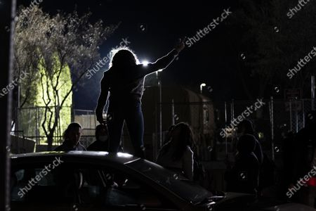A protester raises their middle finger while standing on top of a car outside of the Brooklyn Center Police Department on April 17, 2020. Protests continued for the seventh consectutive night outside the Brooklyn Center Police Department after former officer Kim Porter killed 20-year-old Daunte Wright in a traffic stop.