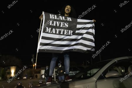 A protester waves a Black Lives Matter Flag on top of a car outside of the Brooklyn Center Police Department on April 17, 2020. Protests continued for the seventh consectutive night outside the Brooklyn Center Police Department after former officer Kim Porter killed 20-year-old Daunte Wright in a traffic stop.