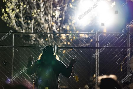 A protester holds onto the fencing outside of the Brooklyn Center Police Department on April 17, 2020. Protests continued for the seventh consectutive night outside the Brooklyn Center Police Department after former officer Kim Porter killed 20-year-old Daunte Wright in a traffic stop.