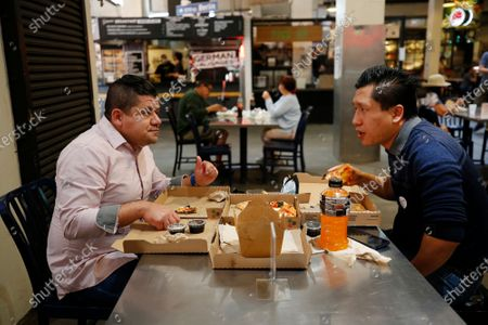 Stock Photo of Los Angeles City workers Harold Arrivillaga, 41, left, and Jason Wong, 38, right, enjoy lunch together at Grand Central Market in downtown Los Angeles as L.A. people talk about their attitudes as L.A. begins to open up. They talk about the spectrum from total shut-in to total freedom and how they see their lives out in public going forward. Los Angeles on Wednesday, April 7, 2021 in Los Angeles, CA. (Al Seib / Los Angeles Times).
