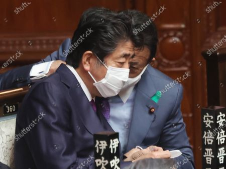 Stock Image of Former Japanese Prime Minister Shinzo Abe (L) chats with Finance Minister Taro Aso (R) at Lower House's plenary session in Tokyo on Tuesday, April 20, 2021. Suga returned from the United States on April 18 as he met with U.S. President Joe Biden as the first foreign leader.