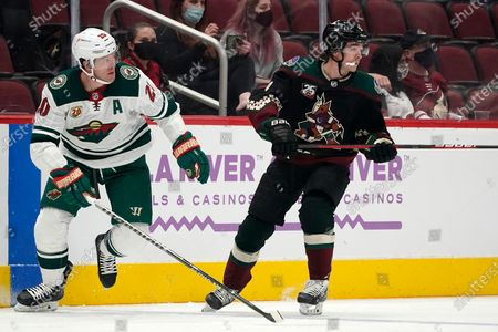 Minnesota Wild defenseman Ryan Suter (20) and Arizona Coyotes right wing Clayton Keller watch the movement of the puck during the first period of an NHL hockey game, in Glendale, Ariz