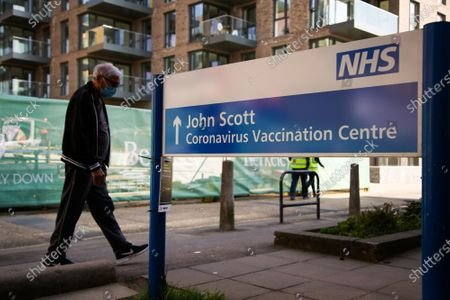 A man walks past the 'JOHN SCOTT CORONAVIURS VACCINATION CENTRE' sign in Hackney, north London, which is closed until Thursday due to vaccine supply shortages.