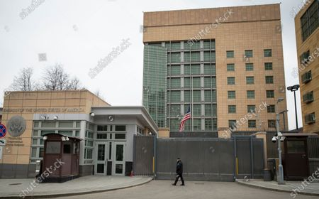 A security staff patrols the U.S. Embassy in Moscow, Russia, . U.S. Ambassador to Russia John Sullivan said Tuesday he will head home for consultations - a move that comes after the Kremlin prodded him to take a break as Washington and Moscow traded sanctions. He emphasized that he would come back to Moscow within weeks
