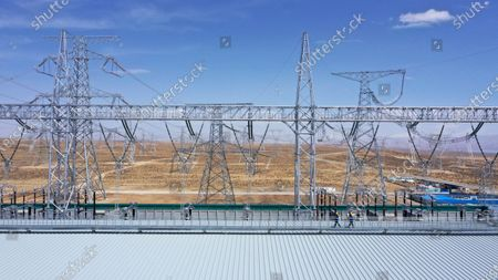 (210420) - XINING, April 20, 2021 (Xinhua) - Aerial photo taken on April 16, 2021 shows a view of a converter station of ultra-high voltage transmission line from Qinghai to Henan, in northwest China's Qinghai Province. The clean power transmission volume of ultra-high voltage link between Qinghai and Henan has hit 10 trillion kilowatt-hours (kWh), according to State Grid Corporation of China (SGCC). The 800-kilovolt direct current transmission line, stretching 1563 kilometers via four provinces, from northwest China's Qinghai, Gansu and Shaanxi provinces to central China's Henan Province, started its operation on December 30, 2020. The transmission line can transmit a total of 40 billion kWh annually at full capacity.