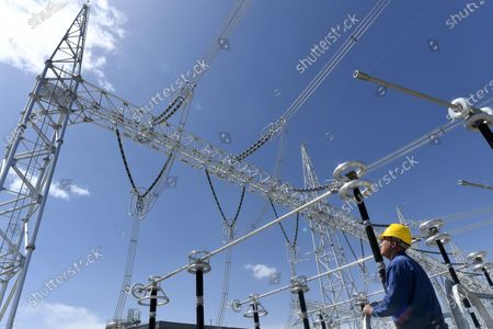 (210420) - XINING, April 20, 2021 (Xinhua) - A worker patrols at a converter station of ultra-high voltage transmission line from Qinghai to Henan, in northwest China's Qinghai Province, April 16, 2021. The clean power transmission volume of ultra-high voltage link between Qinghai and Henan has hit 10 trillion kilowatt-hours (kWh), according to State Grid Corporation of China (SGCC). The 800-kilovolt direct current transmission line, stretching 1563 kilometers via four provinces, from northwest China's Qinghai, Gansu and Shaanxi provinces to central China's Henan Province, started its operation on December 30, 2020. The transmission line can transmit a total of 40 billion kWh annually at full capacity.