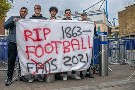 Stock Photo of A goup of unhappy Chelsea supporters protest  with a large banner  outside Stamford Bridge stadium against the decision by Roman Abramovich,the Russian billionaire owner of Chelsea  Football Club  to form a breakaway European Super League with other English Premier Clubs. The decision has created a backlash amongst football supporters nationwide and the government