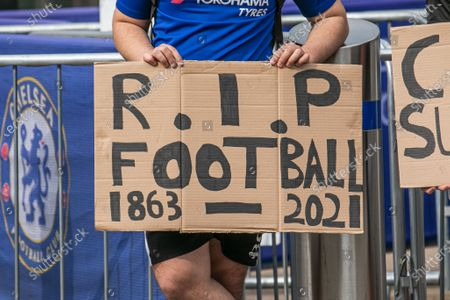 Stock Picture of A goup of unhappy Chelsea supporters protest  with placards outside Stamford Bridge stadium against the decision by Roman Abramovich,the Russian billionaire owner of Chelsea  Football Club  to form a breakaway European Super League with other English Premier Clubs. The decision has created a backlash amongst football supporters nationwide and the government