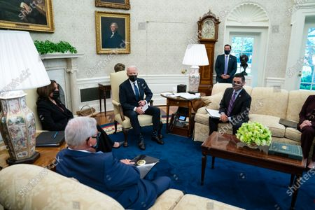 President Joe Biden and Vice President Kamala Harris meet with members of the Congressional Hispanic Caucus, in the Oval Office of the White House, in Washington. Sen. Bob Menendez, D-N.J., and Rep. Raul Ruiz, D-Calif., listen