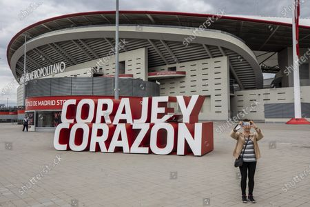"""Woman takes a snapshot in front Atletico Madrid's Wanda Metropolitano stadium in Madrid, Spain, . A group of 12 elite English, Spanish and Italian clubs dramatically split European soccer on Sunday by announcing the formation of a largely-closed Super League. The Super League's founding chairman Florentino Perez on Tuesday, April 20, 2021 says the competition is being created to save soccer for everyone and not to make the rich clubs richer. The Real Madrid president says it's """"impossible"""" that players from the participating teams will be banned by UEFA"""