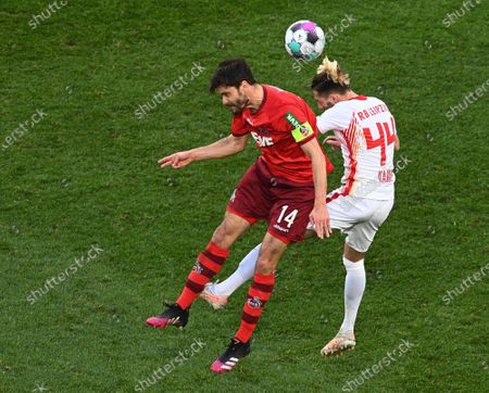 Cologne's Jonas Hector (L) in action against Leipzig's Kevin Kampl (R) during the German Bundesliga soccer match between FC Koeln and RB Leipzig in Cologne, Germany, 20 April 2021.