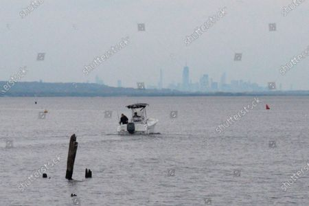 Boat heads out into Raritan Bay in Keyport, N.J., with the New York City skyline on the horizon. A Massachusetts company wants to build a high-voltage power line that would come ashore in Keyport and connect electricity from a future wind farm off the New Jersey coast to the onshore electrical grid