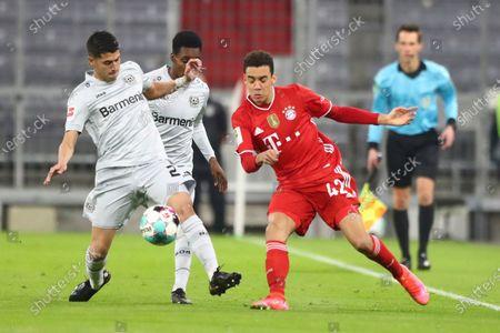 Leverkusen's Mitchell Weiser, left, challenges for the ball with Bayern's Jamal Musiala during the German Bundesliga soccer match between Bayern Munich and Bayer Leverkusen at the Allianz Arena stadium in Munich, Germany