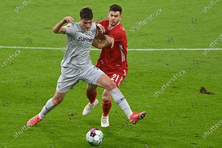 Leverkusen's Patrik Schick, left, challenges for the ball with Bayern's Lucas Hernandez during the German Bundesliga soccer match between Bayern Munich and Bayer Leverkusen at the Allianz Arena stadium in Munich, Germany