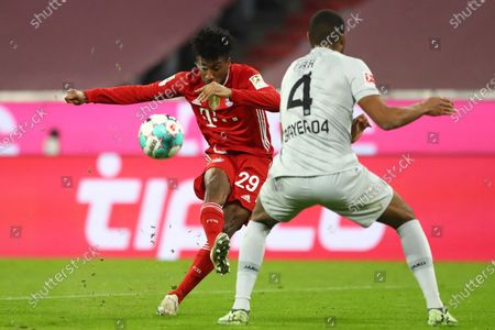 Bayern's Kingsley Coman, left, challenges for the ball with Leverkusen's Jonathan Tah during the German Bundesliga soccer match between Bayern Munich and Bayer Leverkusen at the Allianz Arena stadium in Munich, Germany