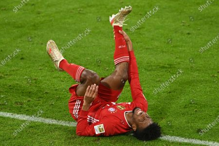 Bayern's Kingsley Coman grimaces after an injury during the German Bundesliga soccer match between Bayern Munich and Bayer Leverkusen at the Allianz Arena stadium in Munich, Germany
